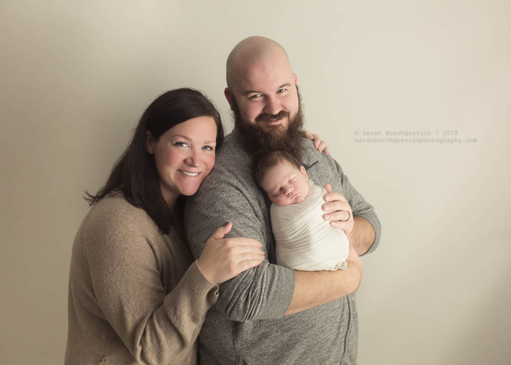 newborn baby with parents on off white background