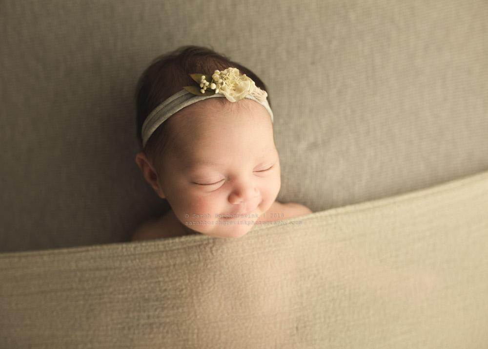 infant girl smiling in her sleep