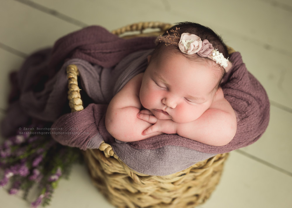 Newborn girl posed in basket