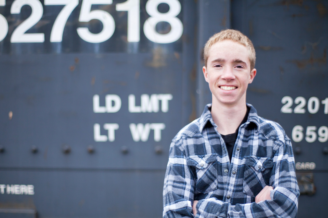 4-Senior-Portrait-Photography-Ken-Bruggeman-York-PA-Young-Man-Smiling-Train-Numbers.jpg