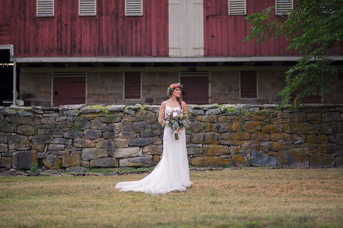 28-Bride-Standing-Historic-Red-Stone-Barn.jpg