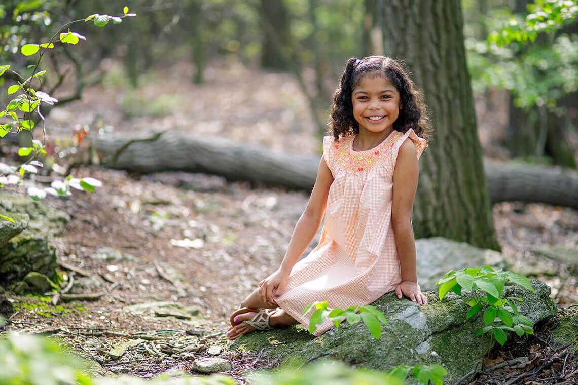 1-Family-Photographer-York_PA-Ken-Bruggeman-Photography-Young-Girl-Sitting-Rock-Smiling.jpg