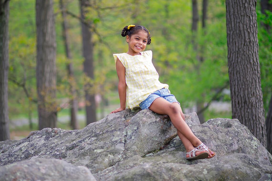 10-Family-Photographer-York_PA-Ken-Bruggeman-Photography-Young-Girl-Sitting-Rock-Smiling-Yellow-Shirt-Braids.jpg