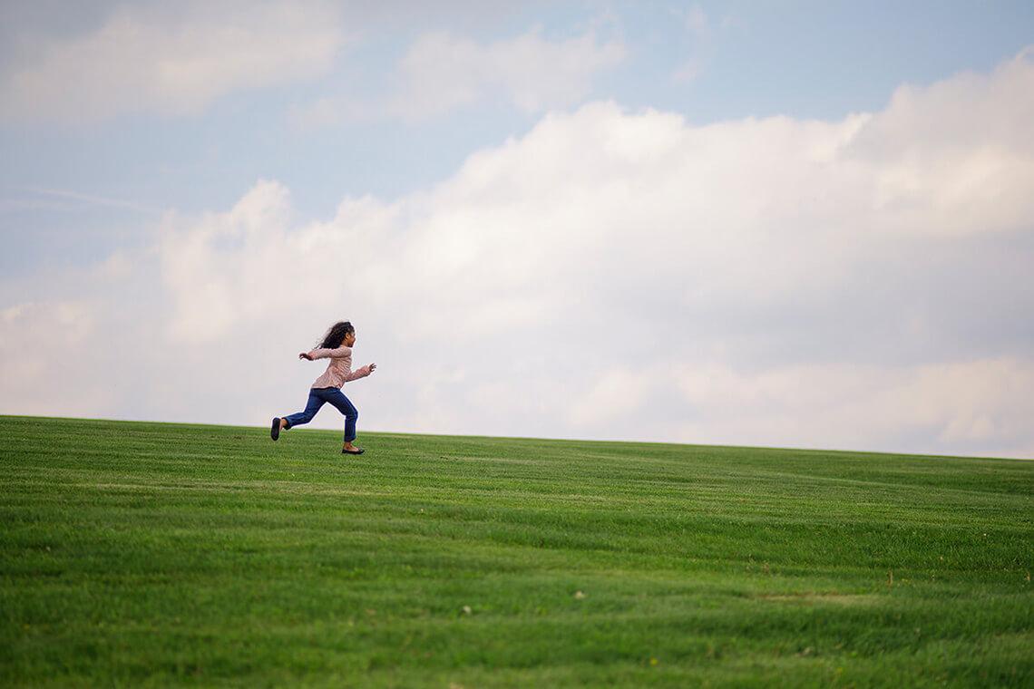 11-Family-Photographer-York_PA-Ken-Bruggeman-Photography-Young-Girl-Running-Park-Green-Grass-Blue-Sky.jpg