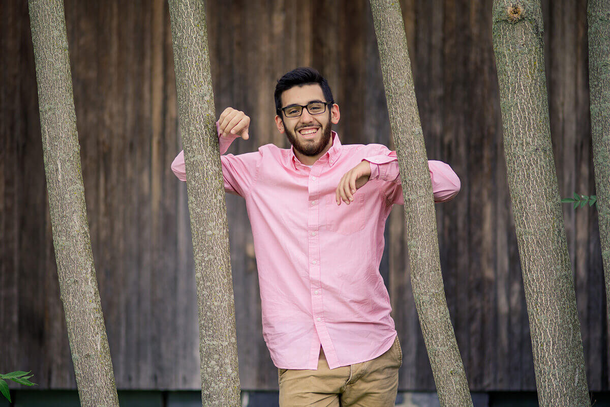 7-Senior-Portrait-Photographer-York-PA-Ken-Bruggeman-Photography-Young-Man-Pink-Shirt-Smiling-Arms-On-Trees.jpg