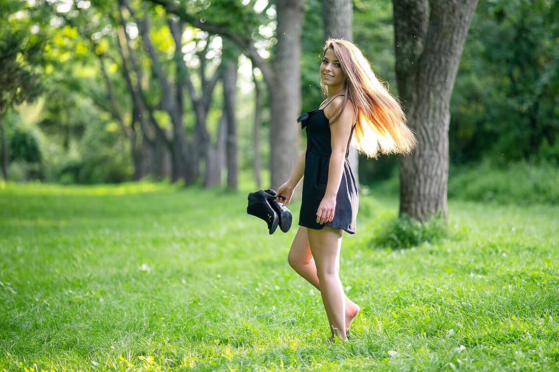 7-Senior-Portrait-Photographer-York-PA-Ken-Bruggeman-Photography-Girl-Twirling-Black-Dress-Green-Grass-Trees-Laughing.jpg