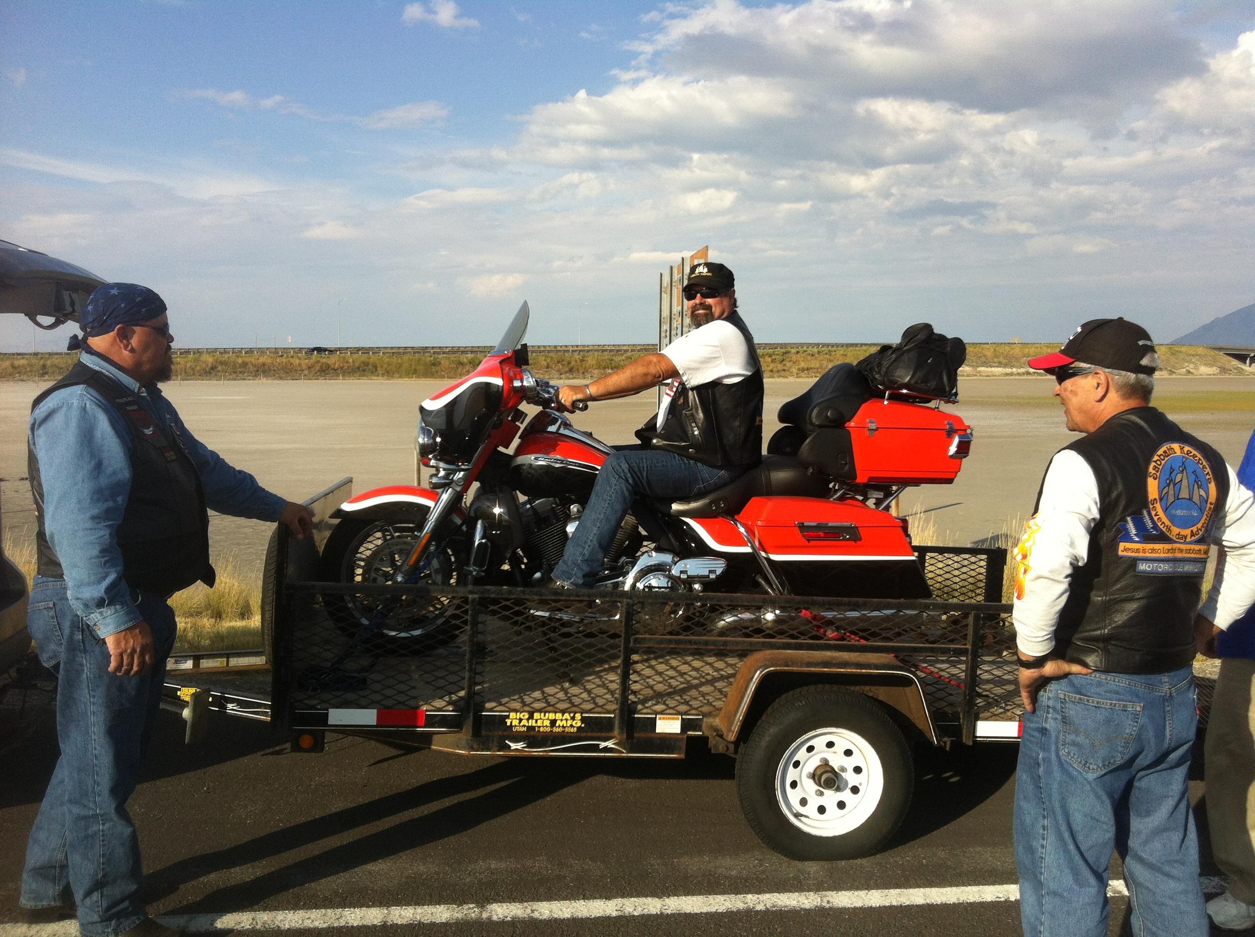 From left to right: Keith Cordis, Tony Lambert, andAkira Toyama. Tony loads his bike onto Dave Holland's trailer.