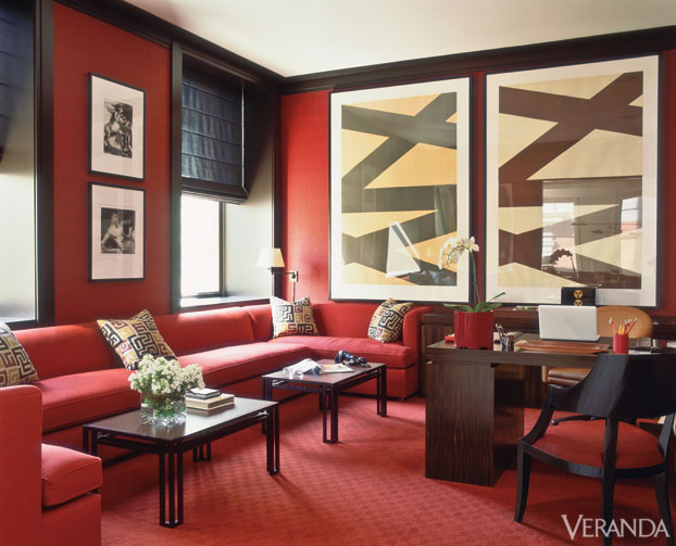 Allover red makes a bold statement, accentuated by accents in black.  Using a single red tone means that the walls, sectional sofa, and floor run together visually.  Design by Carl Steele, as featured in Veranda.