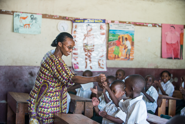©2014 Ni Nyaminga/Girl Hub. All Rights Reserved. Floride Basabose celebrates a correct answer with her students.  Her school was built by a group of mothers who were determined that the children get a better education.