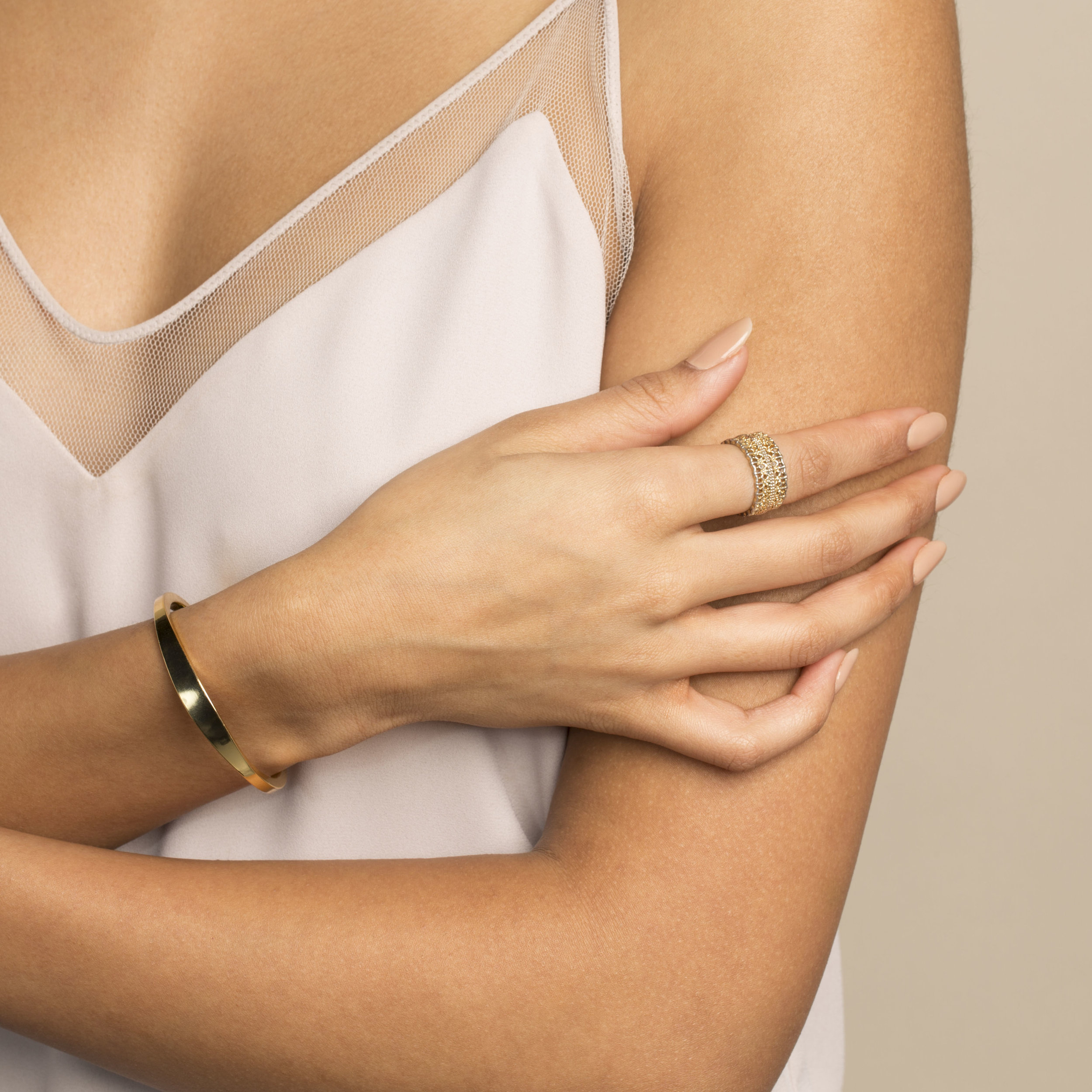 young brown skinned model with manicure wearing camisole, gold bracelet and ring