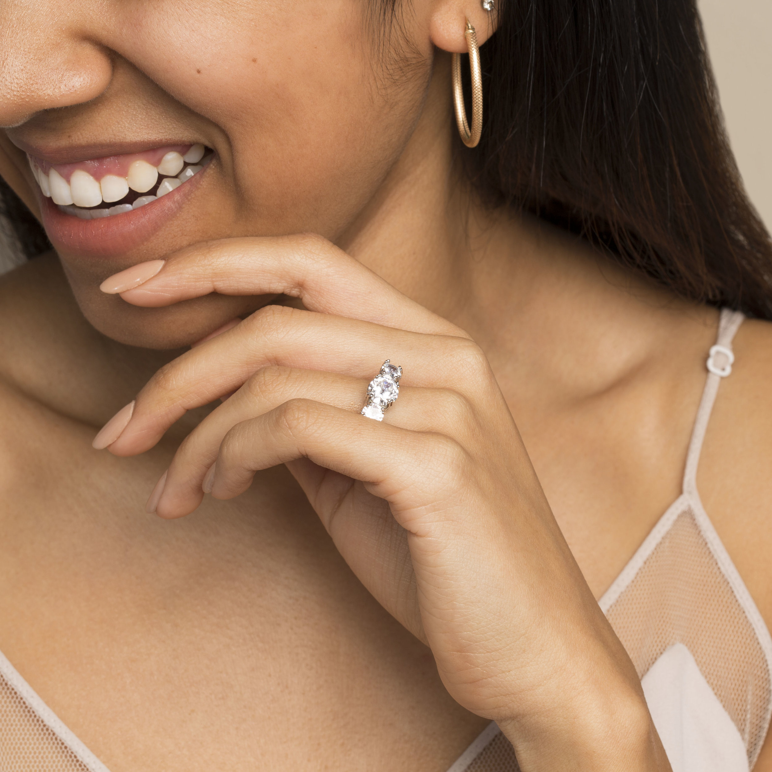 young brown model smiling wearing engagement ring with manicured nails