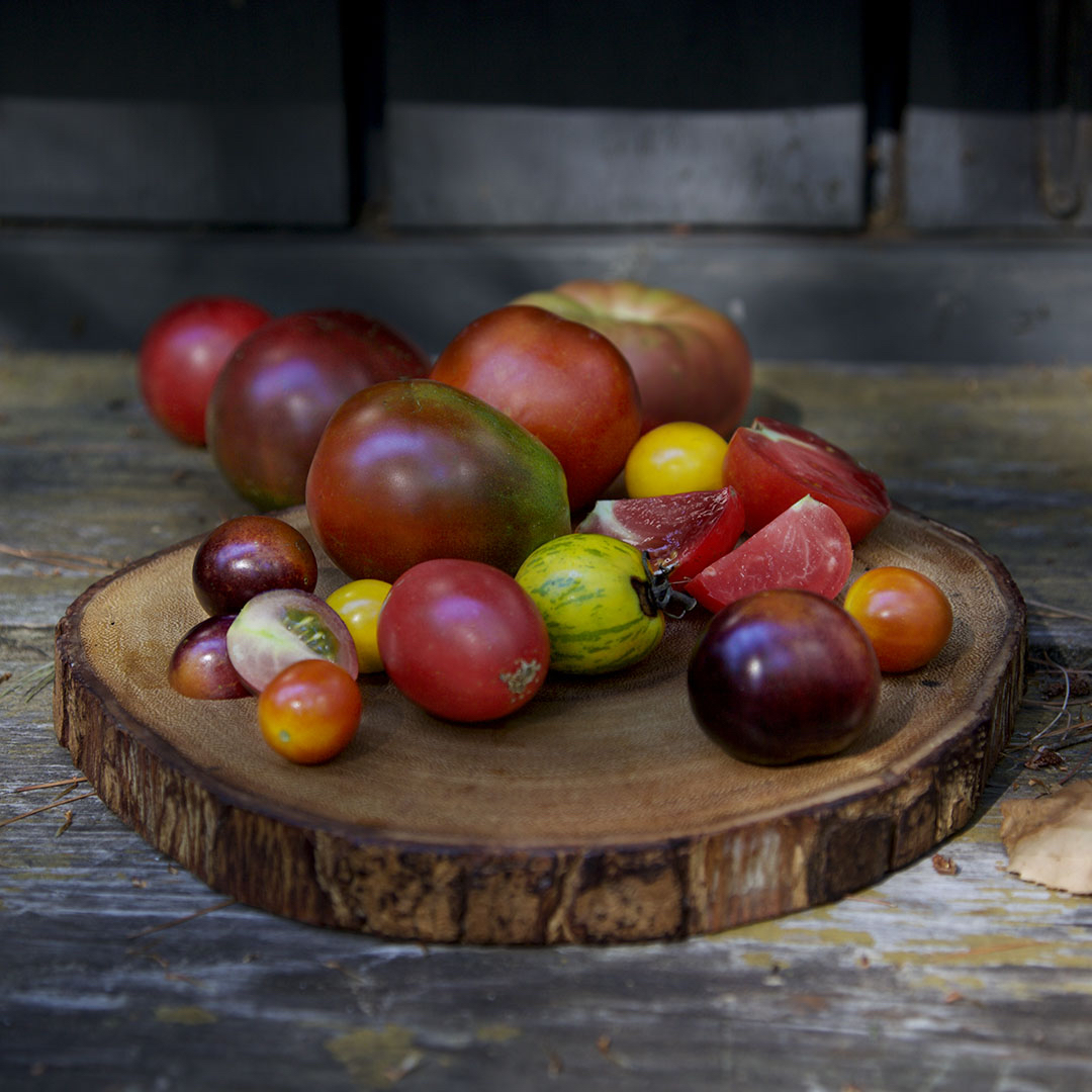 seasonal heirloom tomotes on sliced log charger