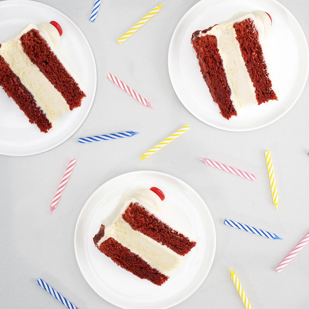 Three slices of red velvet cheesecake torte cake with scattered birthday candles