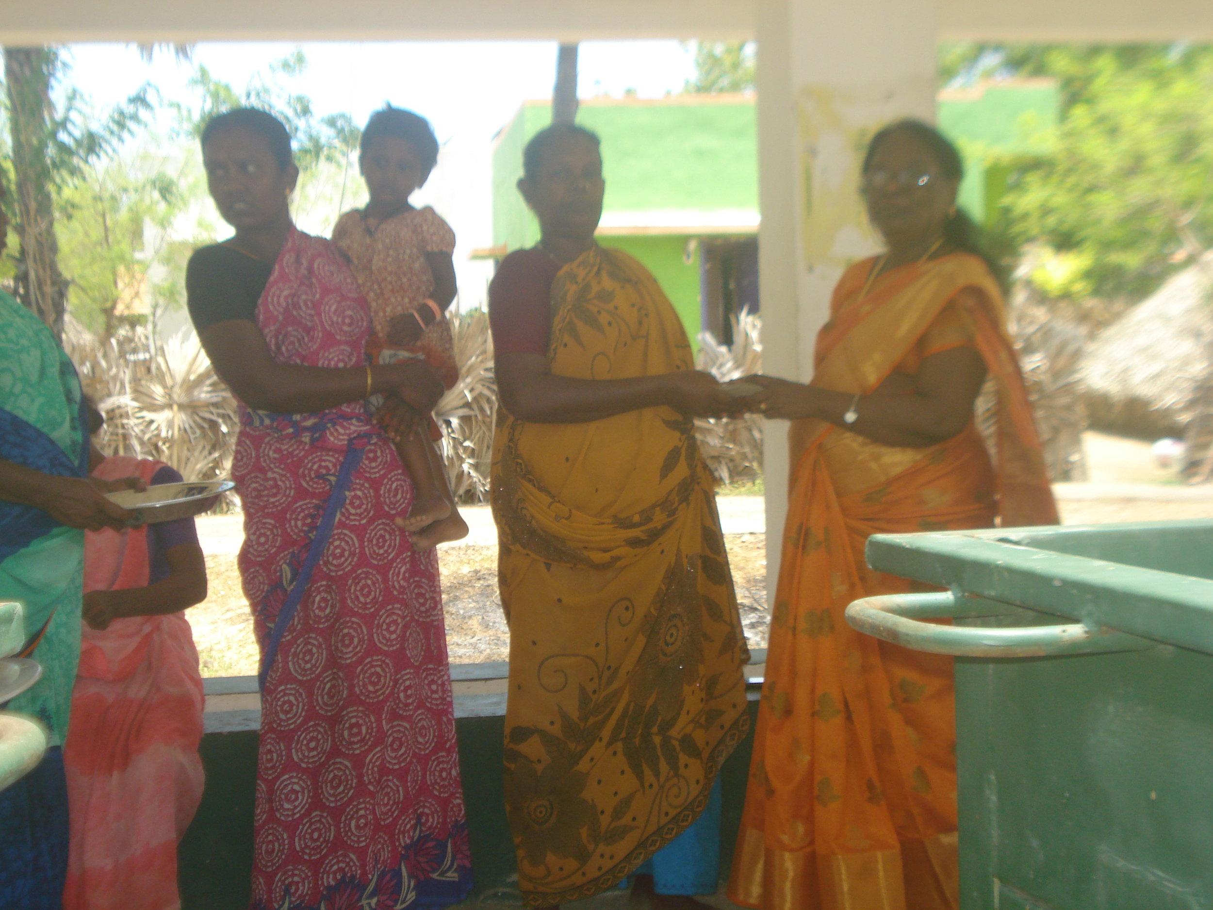 Health Coordinator Jansi Rani distributing credit assistance to Ms. Sarojamary for sea weed program.