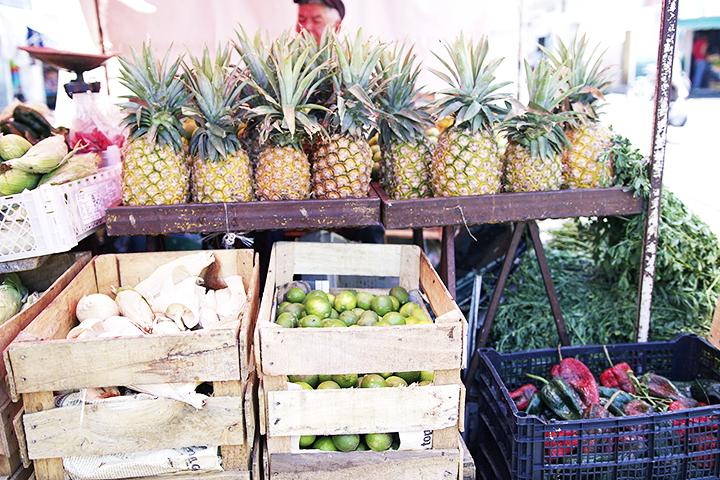 Here's a photo of a fruit and veggie stand in the mercado. This man sold the prettiest pineapples..  Aquí hay una foto de un puesto de frutas y de vegetales en el Mercado. Este señor vendía las piñas más bonitas..