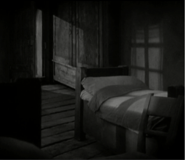 Image 1. The dark, empty room. The wife's bed is given importance by the function of the lighting and composition, her bed occupies the frame while the husband's is cropped out. It is also well lit with high key lighting, with the image of a cross made by the shadow of the window, a symbol of the good nature of the wife thought to be deceased. Light also enters through the doorway in the background, providing a low-key light for the floorboards, giving a sense of depth to the room.