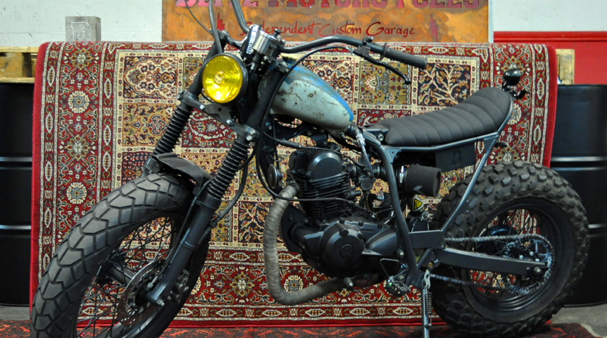 The donor bike is a Yamaha 125 cc TW: - The whole bike has been matt dark grey powder coated; - the subframe has been bespoke made (shortened by over 30 cm).