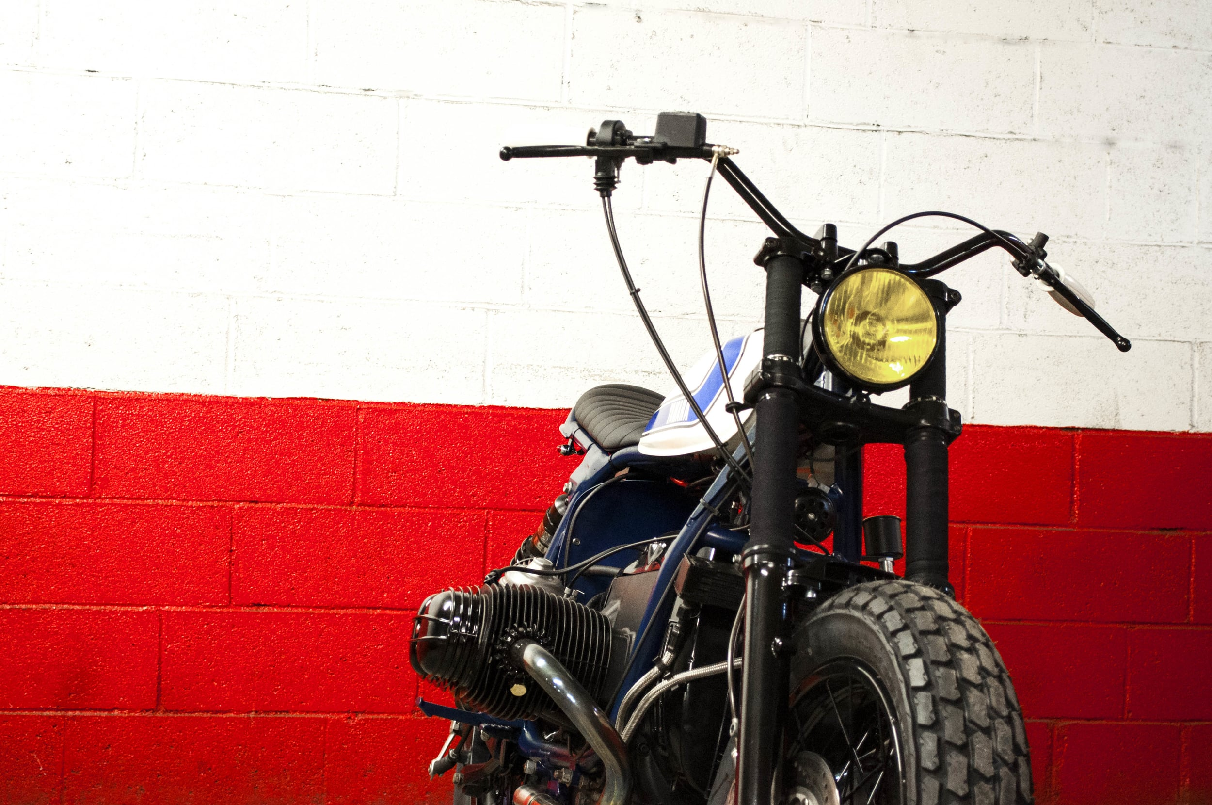 - Vintage yellow headlight from the 70's adpated on the bespoke electric wiring;  -  Triumph  handlebar.
