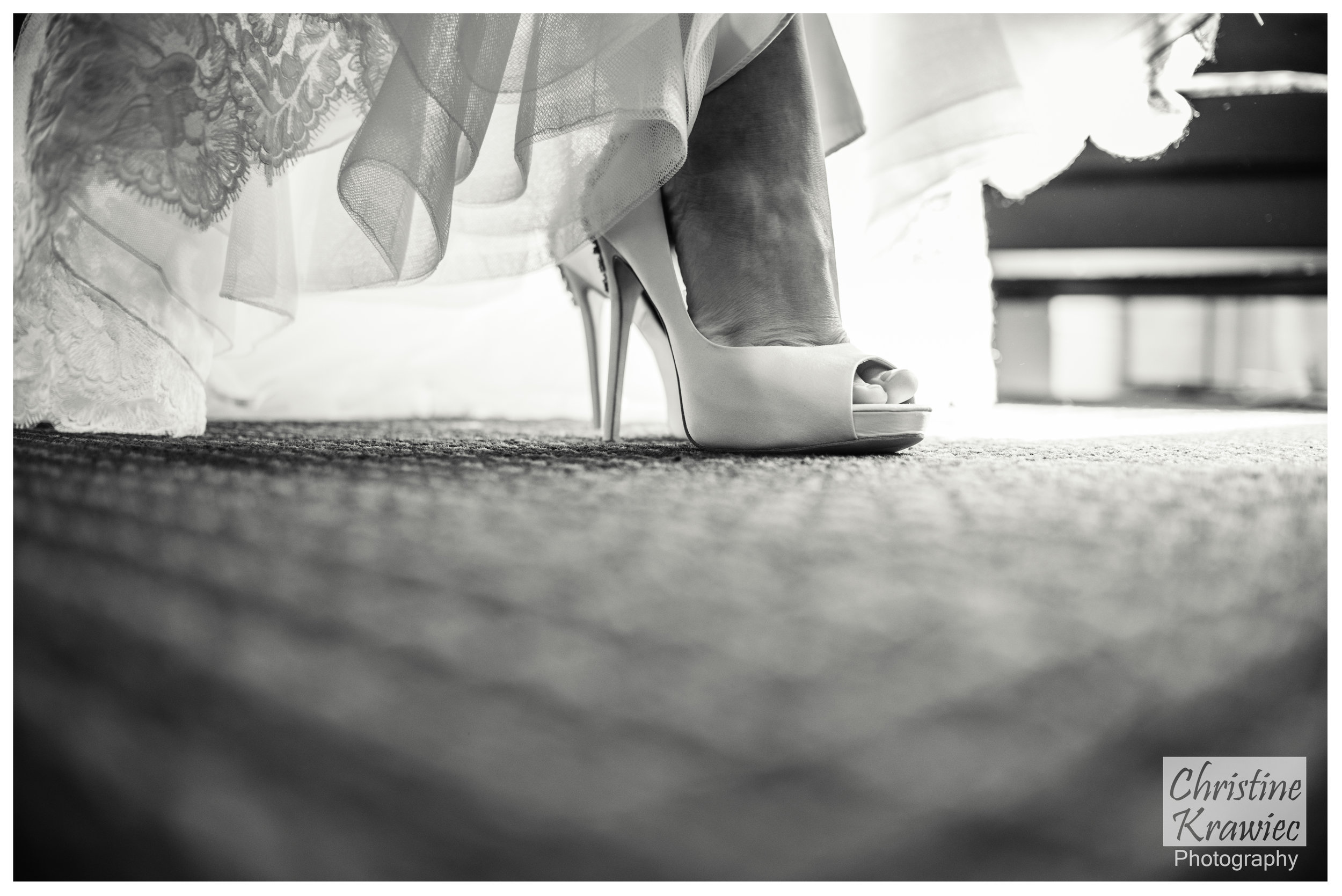 Last minute details while slipping on her wedding shoes