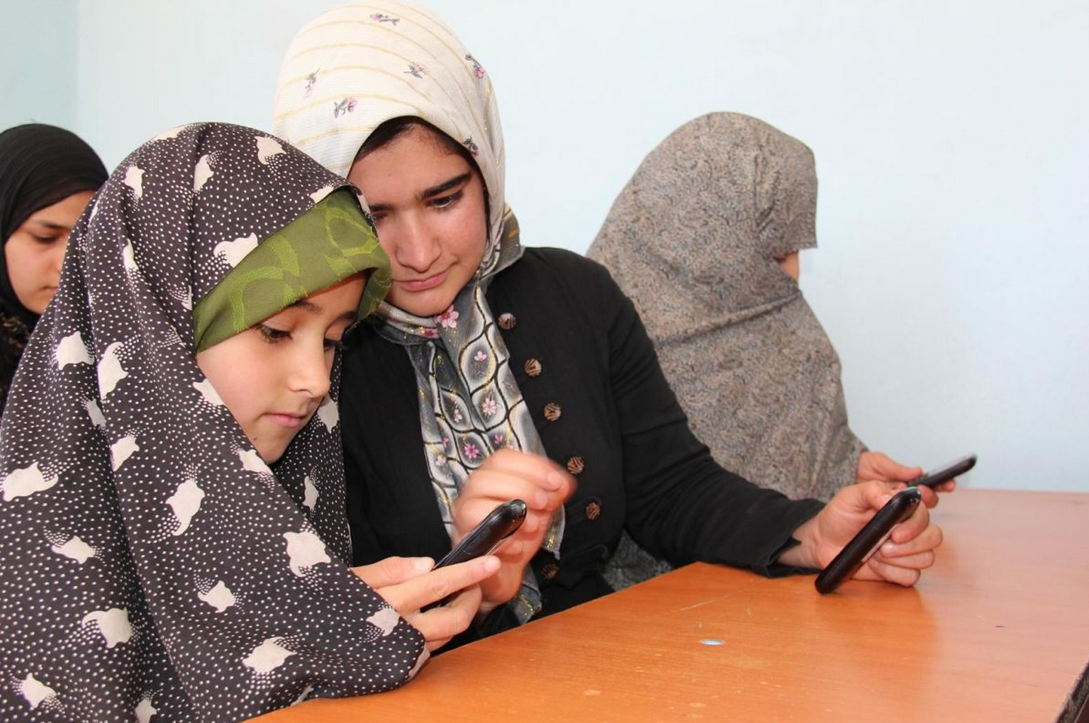 Afghan girls learning to read with mobile phones.