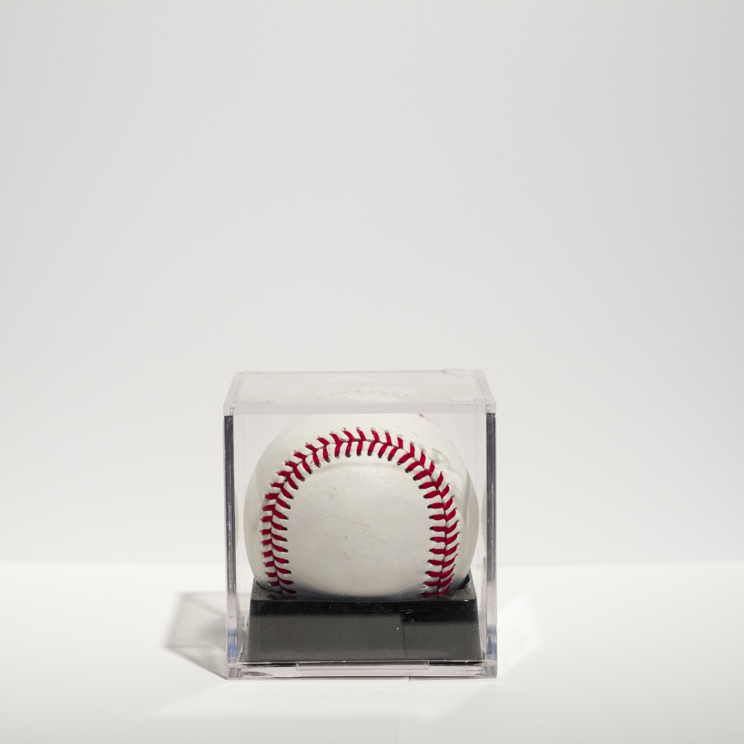 "Coconut (I),    —  3"" x 3"" x 3"" baseball filled with artists hair in memorabilia case."