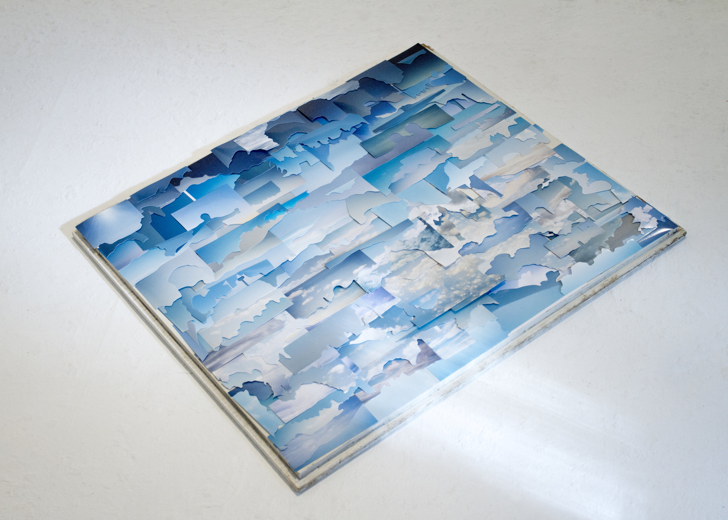 """The Sky IS Falling —   23"""" x 27"""" panel — blue skies from discarded family photographs purchased at thrift stores."""