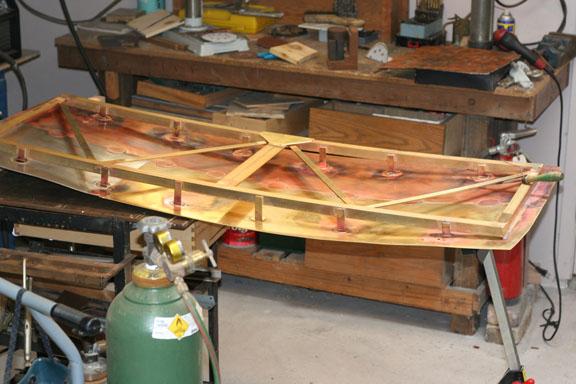 Showing an all metal framework behind a sculptural piece.