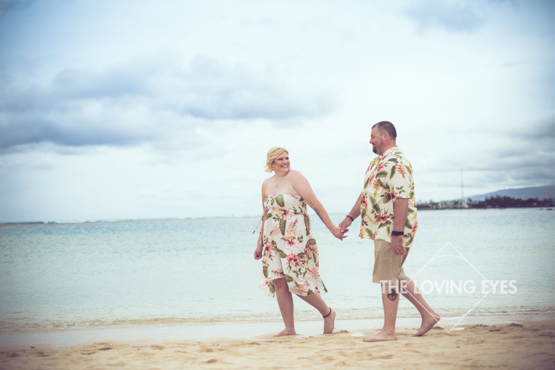 Walking hand in hand on the beach during Hawaii vacation at Ala Moana Beach Park