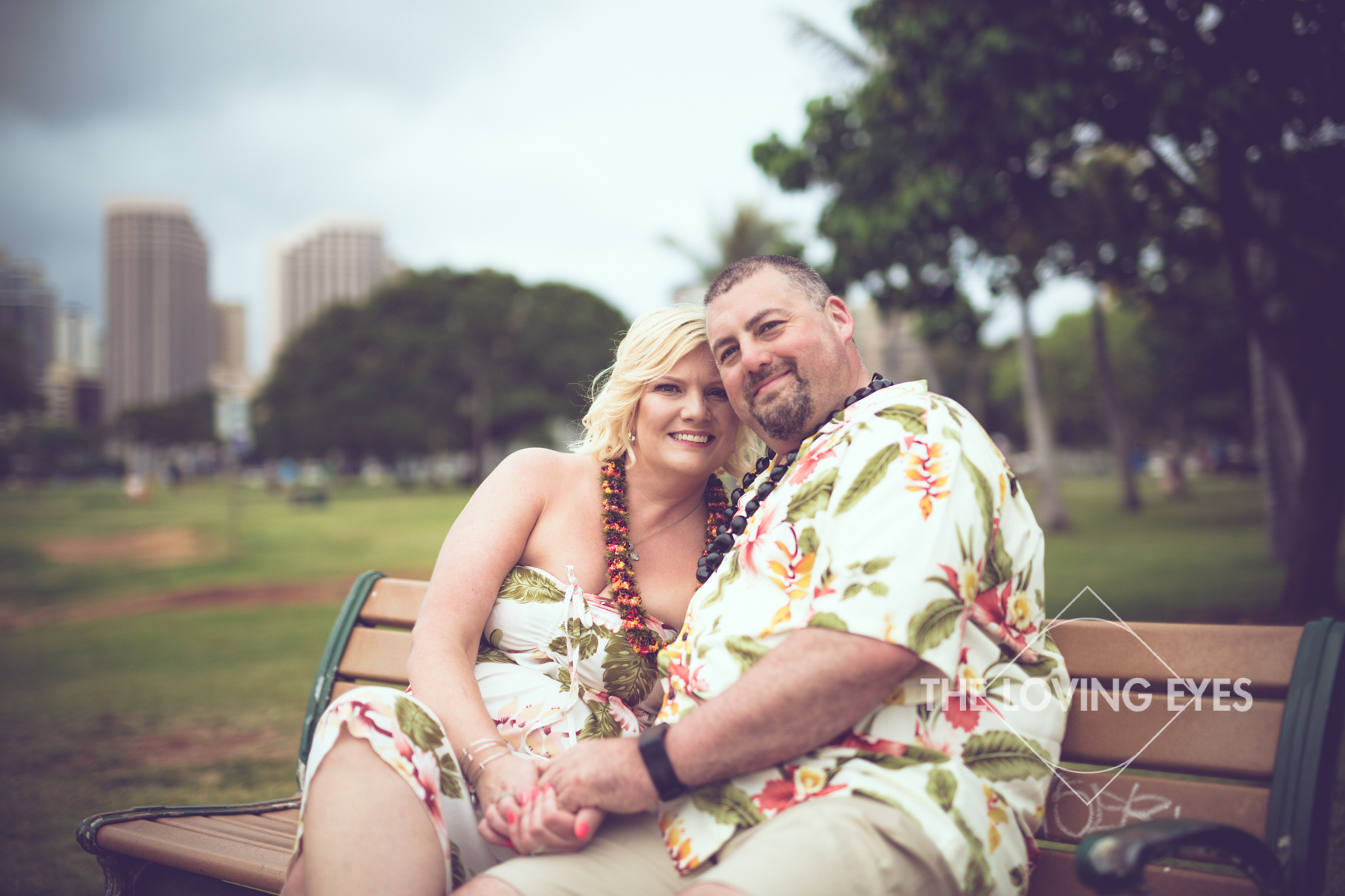 Sitting together on a park bench on the beach during Hawaii vacation at Ala Moana Beach Park