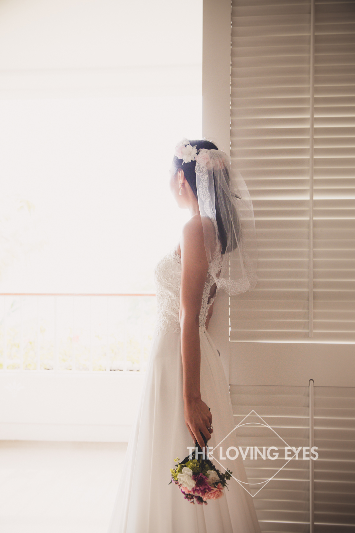 Bride looking out the window at the Four Seasons Resort at Ko Olina after getting dressed
