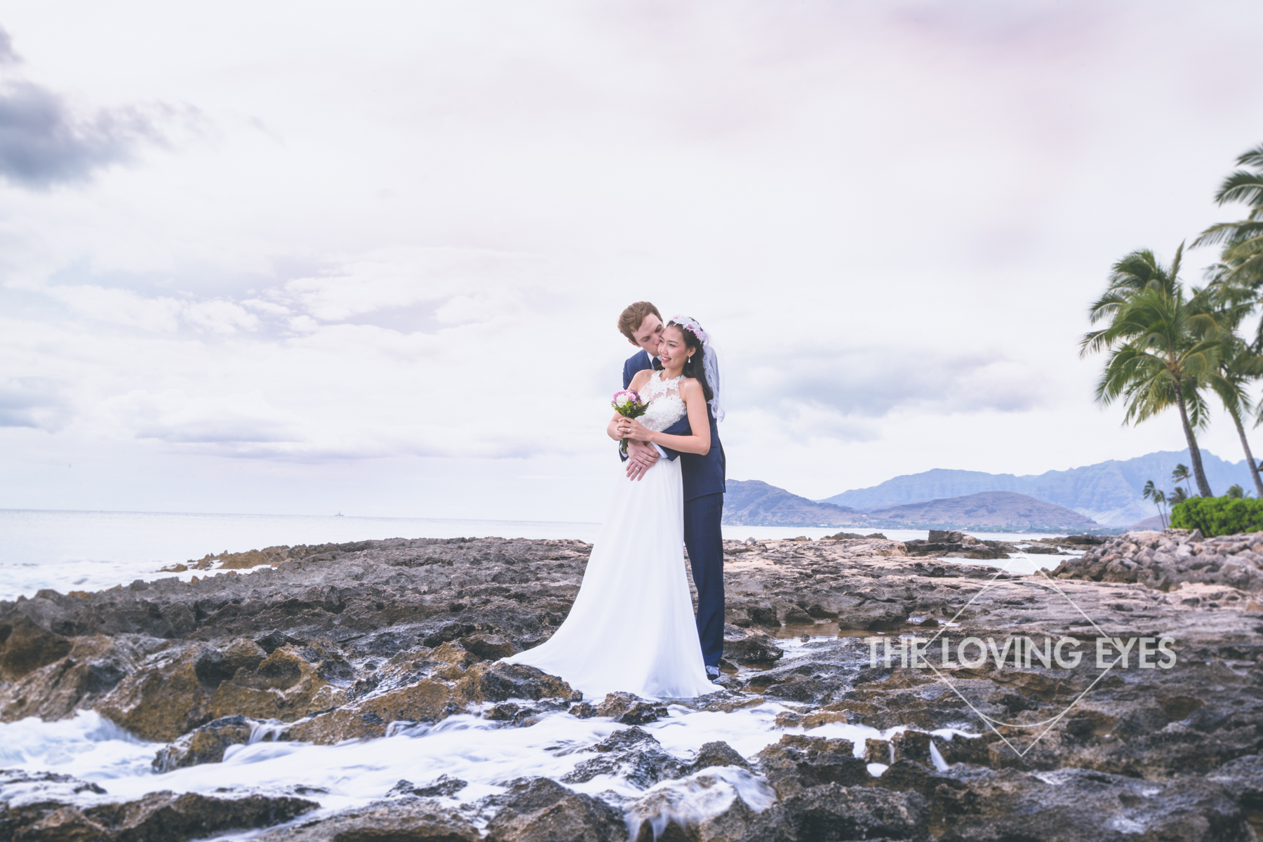 Bride and groom embracing in the waves during sunset at the lagoon near the Four Seasons Resort at Ko Olina