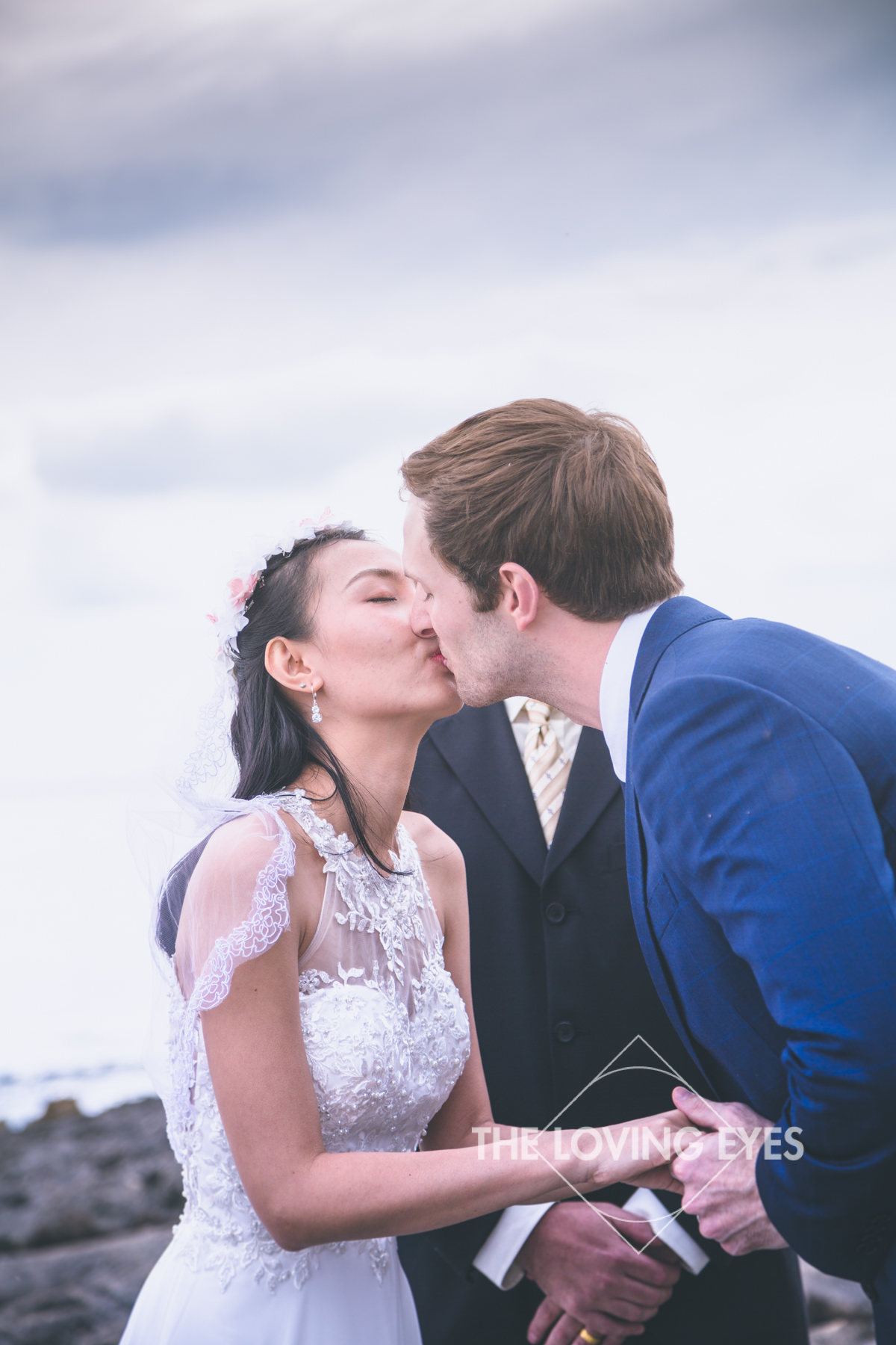 Bride and groom's first kiss at their intimate wedding ceremony at the lagoon near the Four Seasons Resort at Ko Olina