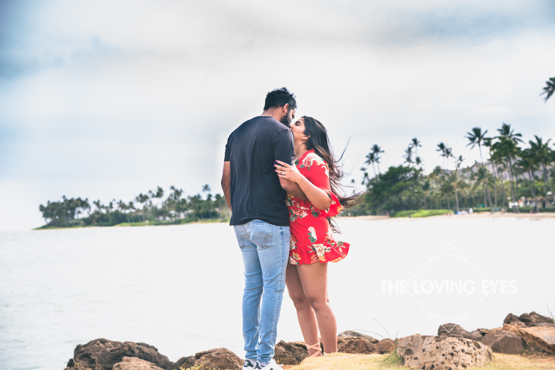 Couple embracing each other at Waialae Beach Park while on vacation in Hawaii