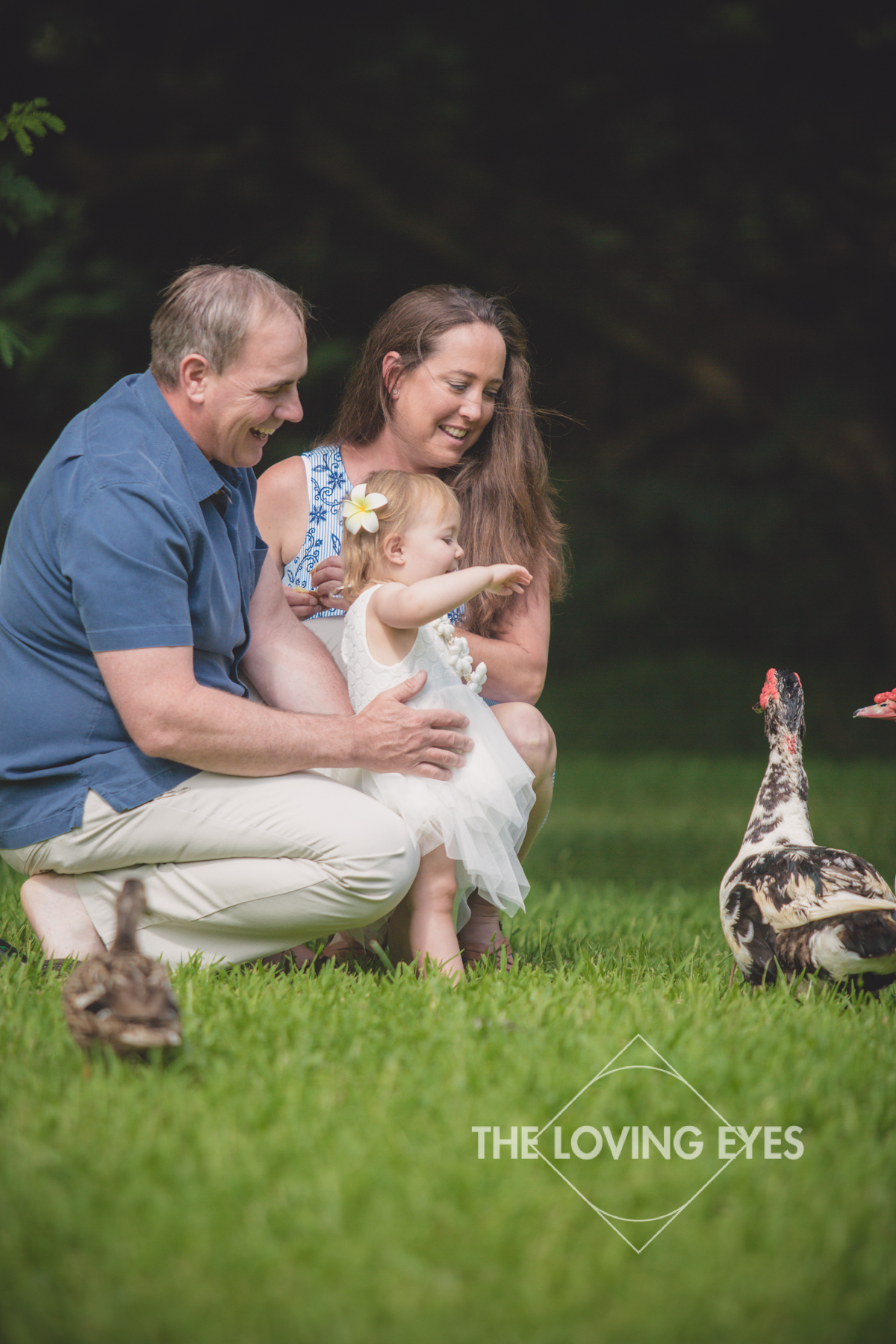 Family portrait during vacation with ducks and geese at Hoʻomaluhia Botanical Gardens