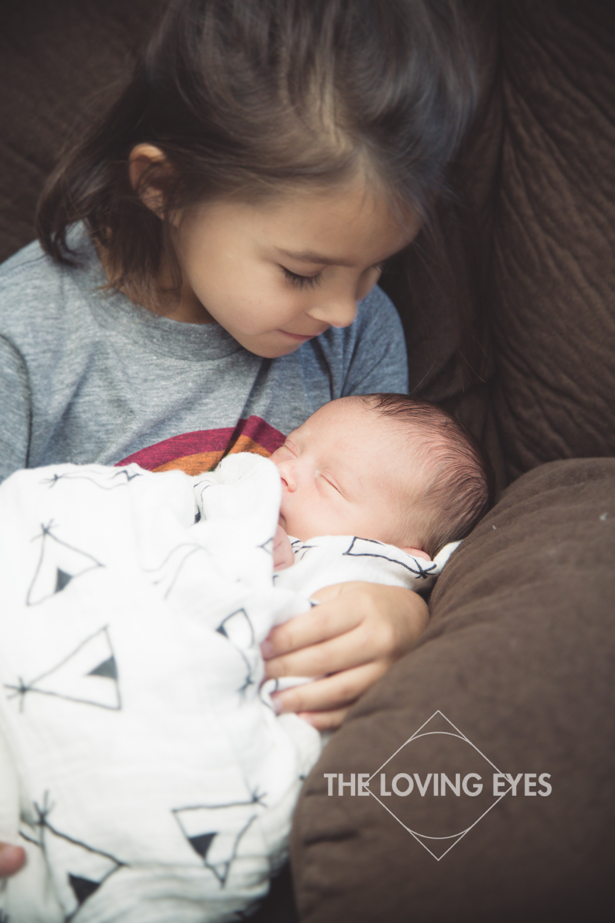 Hawaii newborn photography swaddled and sleeping baby in home with family adored by big sister