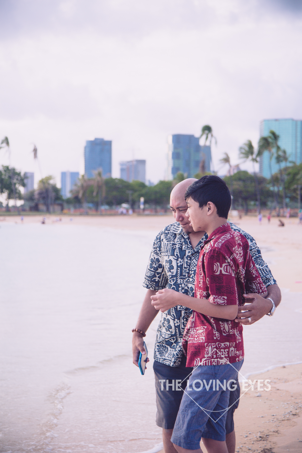 Father and son playing on the beach at Ala Moana Beach Park in Hawaii