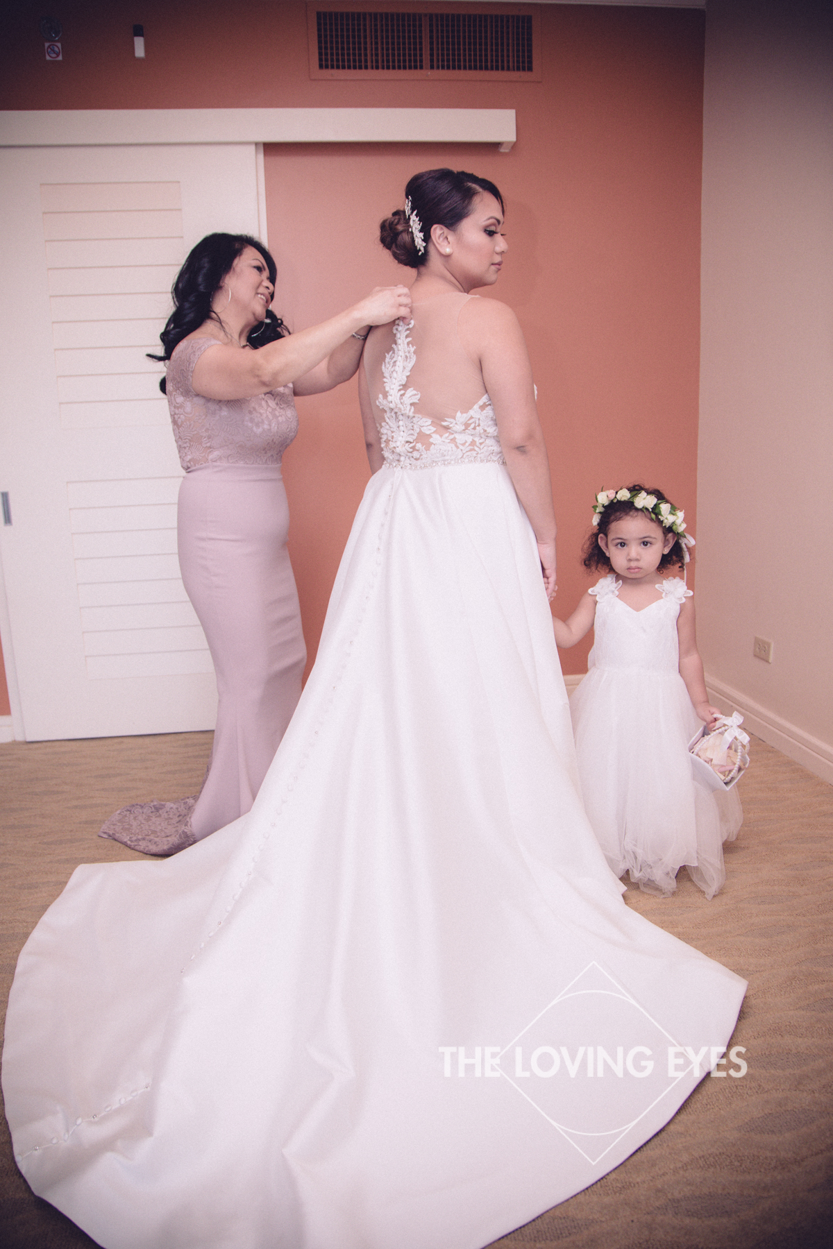 Bride with mother and flower girl on wedding day getting ready in wedding dress