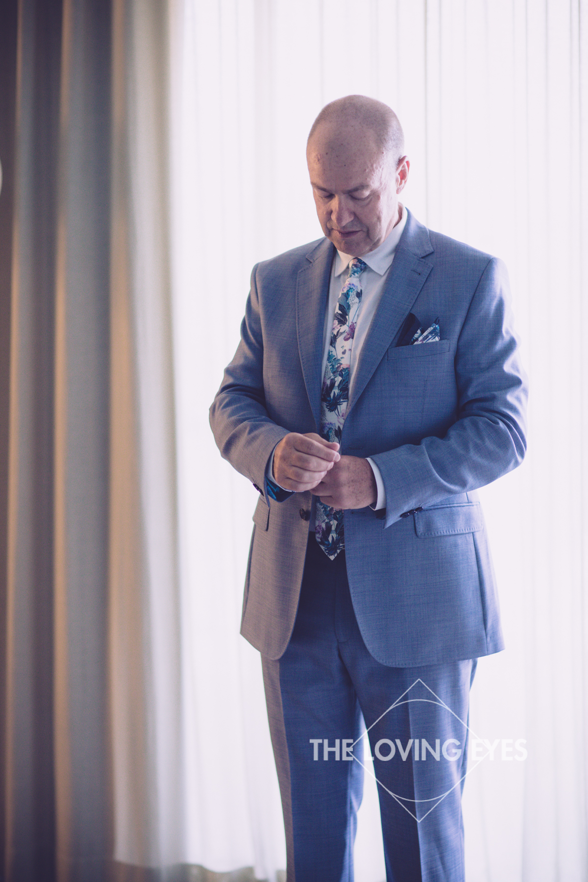 Groom getting dressed for wedding ceremony in Hawaii