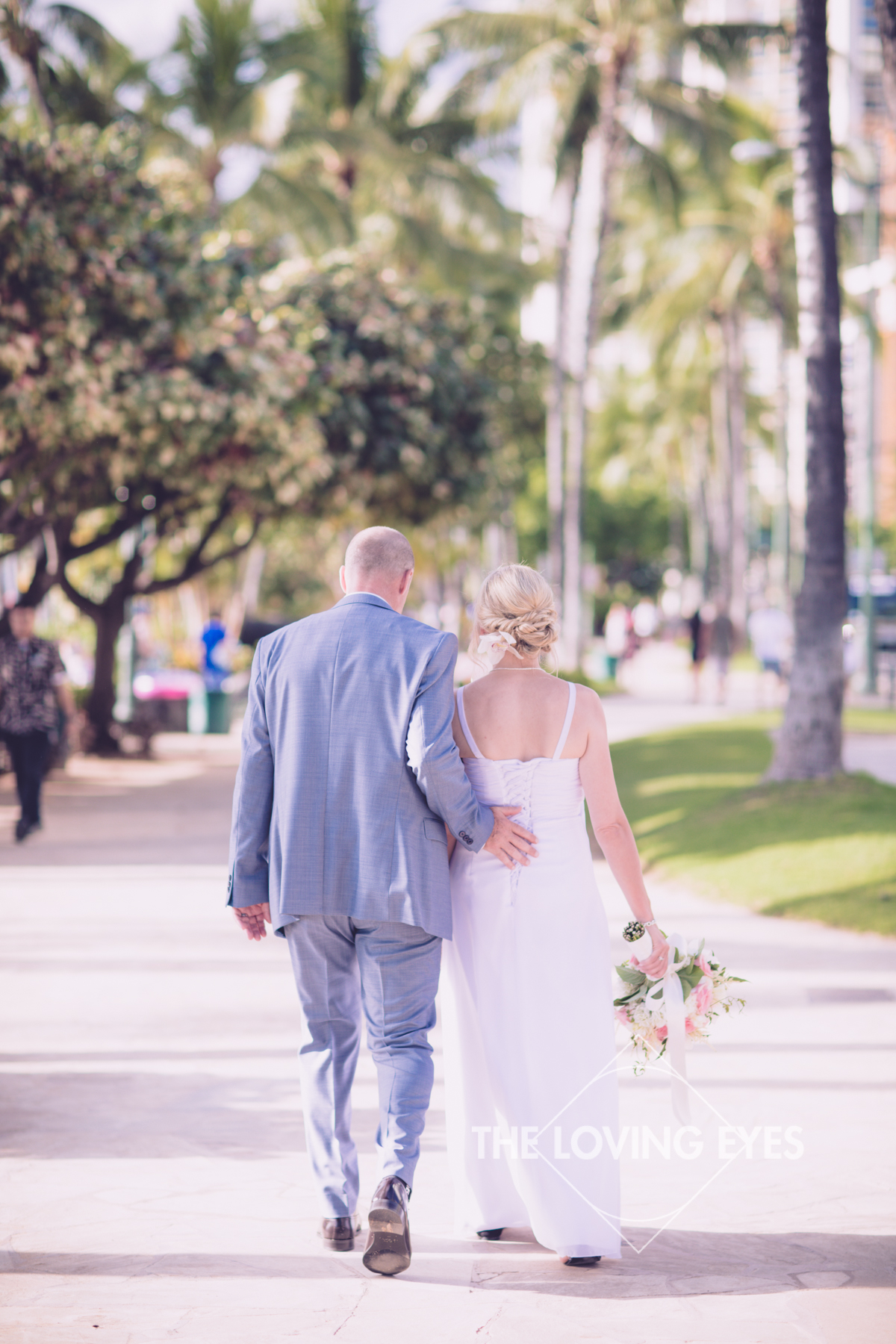 Bride and groom on their wedding day strolling in Waikiki