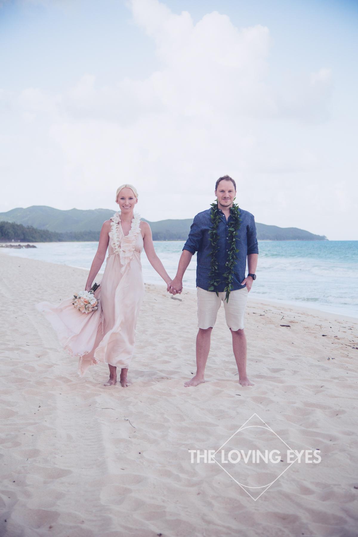 Bride and groom on white sandy beach during Hawaiian beach elopement