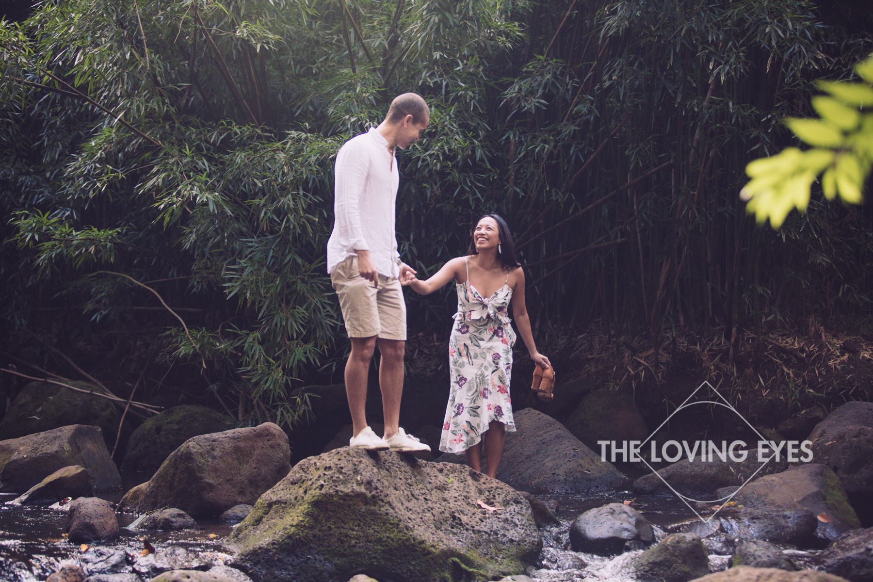 Engagement photos in a bamboo forest stream in Hawaii
