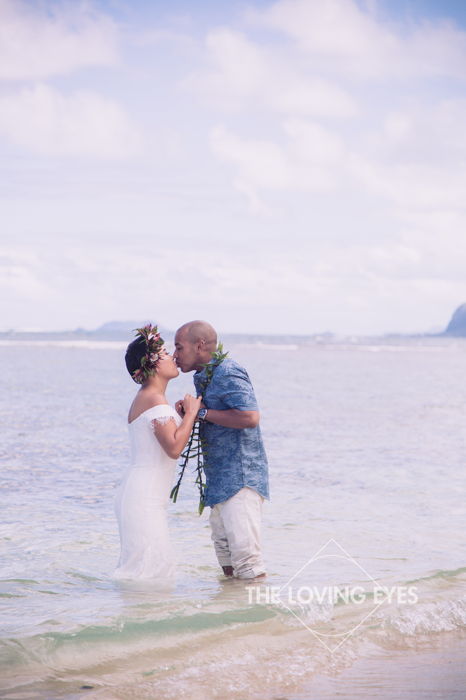 Romantic bride and groom portrait in the water on the beach at the Tiki Moon Villas in Hawaii