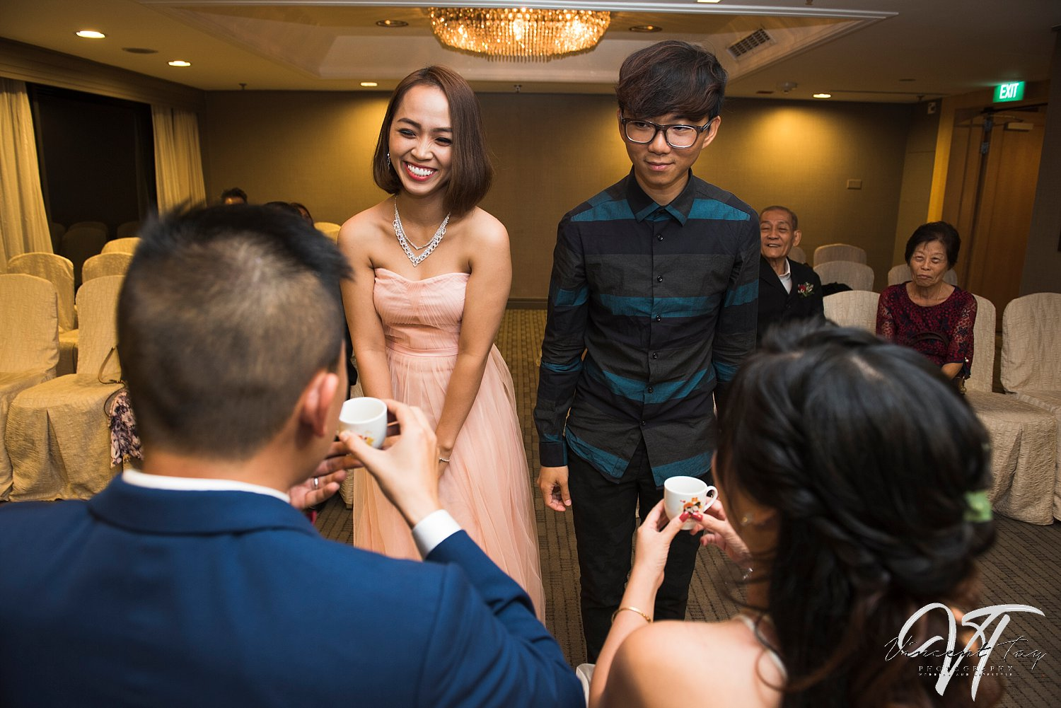 Actual Day Wedding Photography Singapore: Couple offering the tea to the groom's father. A ceremony to show that they are as one family now.