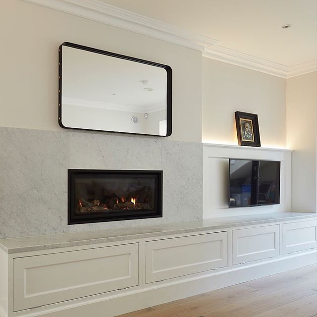The beautiful leather and stud detail on this adnet mirror introduces luxurious texture to the carerra marble fire surround #adnetmirror #gubi #homedecor #fireplace #contemporaryfireplace #irishdesign @gubiofficial