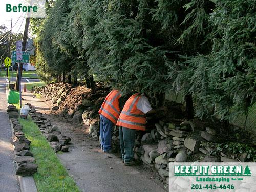 Landscape technicians disassemble stone wall in disrepair. Glen Rock, NJ 07452