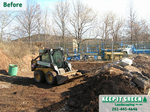 Loader operator clearing construction debris and grading site. Clifton, NJ 07014