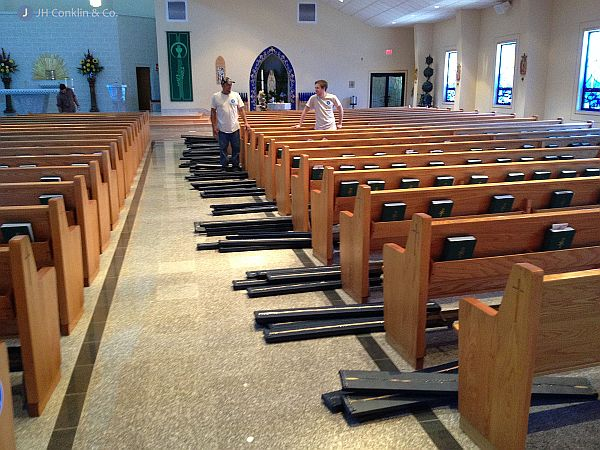 Installing re-upholstered pads in the pews.