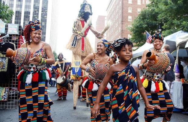 Dancers in kente cloth with shekeres and stilt walker parade down Fayetteville Street