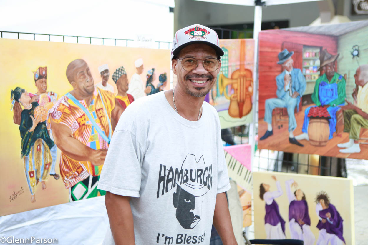 artist LeGrant Taylor in front of his paintings Art Gallery Walk
