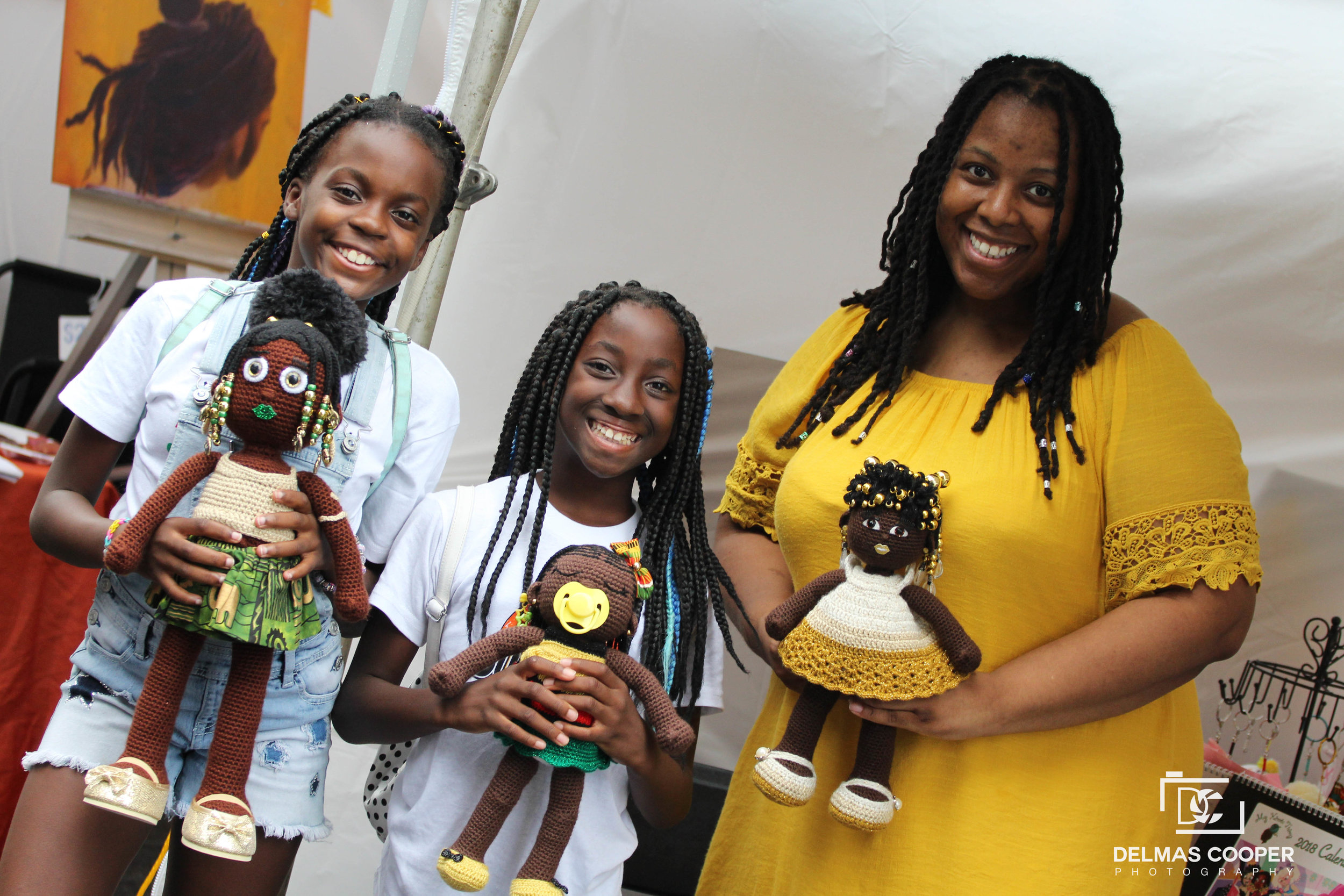 dollmaker Aniqua Wilkerson and two girls holding her handmade dolls